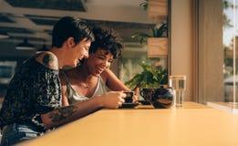 Amis en café utilisant le téléphone portable Photos libres de droits