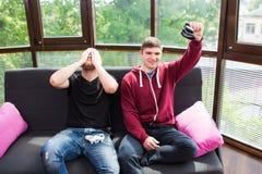 Amis en jouant des jeux vidéo Photo stock