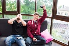 Amis en jouant des jeux vidéo Images libres de droits