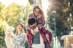 Amis en parc ayant l'amusement avec le chiot mignon Photographie stock libre de droits