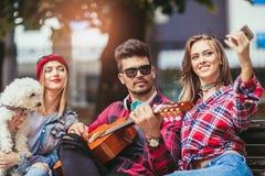 Amis en parc ayant l'amusement jouant la guitare Image libre de droits