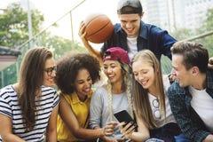 Amis en parc regardant utilisant les smartphones millénaires et vous Image stock
