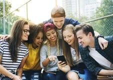 Amis en parc regardant utilisant les smartphones millénaires et vous Images libres de droits