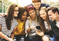 Amis en parc regardant utilisant les smartphones millénaires et vous Photographie stock