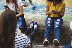 Amis en parc utilisant des smartphones Photo libre de droits