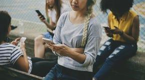 Amis en parc utilisant des smartphones Photographie stock libre de droits