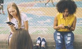 Amis en parc utilisant des smartphones Photos stock