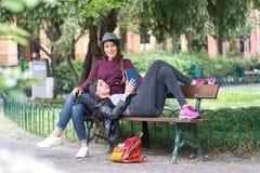 Amis en vacances détendant sur un banc lisant un livre Photographie stock libre de droits