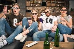 Amis en verres 3D observant le film Images libres de droits