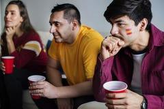 Amis encourageant la coupe du monde avec le drapeau peint Image stock