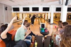 Amis encourageant le bowling de femme dans le club Image libre de droits