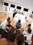Amis encourageant le bowling de femme dans le club Photographie stock libre de droits