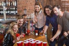 Amis encourageant tandis que femme jouant la puanteur de bière dans la barre Images libres de droits