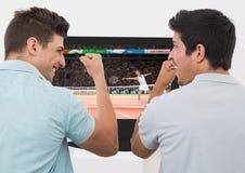 Amis encourageant tout en regardant la rencontre de tennis à la télévision Photo libre de droits