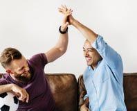 Amis encourageant un jeu à la télévision ensemble Photos stock