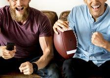 Amis encourageant un jeu à la télévision ensemble Images libres de droits