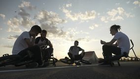 Amis ennuyés fatigués avec des vélos retirant sa candidature sur la rue utilisant des smartphones avec le coucher du soleil et le clips vidéos