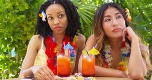Amis ennuyés s'asseyant à la table des vacances tropicales Image stock