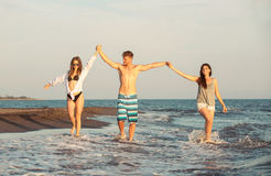 Amis ensemble sur la plage ayant l'amusement Photographie stock libre de droits