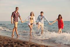 Amis ensemble sur la plage ayant l'amusement Image stock