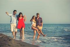 Amis ensemble sur la plage ayant l'amusement Image libre de droits