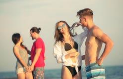 Amis ensemble sur la plage ayant l'amusement Photographie stock