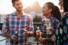 Amis ensemble sur le dessus de toit avec des boissons Image stock