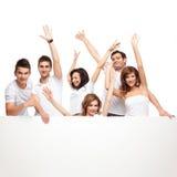 Amis enthousiastes annonçant le panneau blanc Photo stock