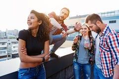 Amis enthousiastes ayant l'amusement sur le toit Photo libre de droits