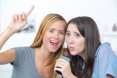 Amis enthousiastes chantant sur le divan à la maison Images stock