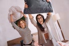 Amis enthousiastes drôles ratant son coup autour dans le lit Image libre de droits