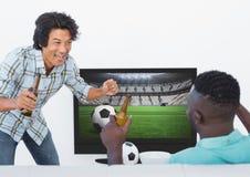 Amis enthousiastes observant le match de football tout en ayant la bière Image stock