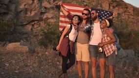 Amis enthousiastes posant parmi des roches avec le drapeau Photographie stock libre de droits