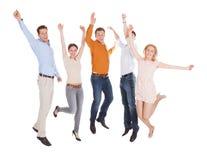 Amis enthousiastes sautant par-dessus le fond blanc Photographie stock