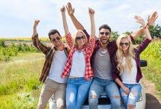 Amis enthousiastes sur le sourire extérieur de personnes de bras d'augmenter de campagne de voiture tenant des mains  Photo libre de droits