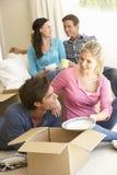 Amis entrant dans la nouvelle maison déballant des boîtes Photos stock