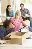 Amis entrant dans la nouvelle maison déballant des boîtes Photo libre de droits