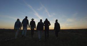 Amis entrant ensemble dans le coucher de soleil photo stock
