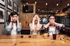 Amis espiègles couvrant leurs visages Image libre de droits