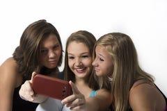 Amis espiègles d'adolescent prenant des selfies de groupe Image stock