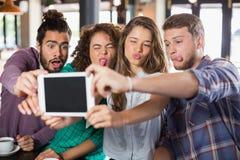 Amis espiègles prenant le selfie avec le comprimé numérique Photo stock