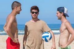 Amis essayant de jouer la boule de volée sur la plage Photos libres de droits