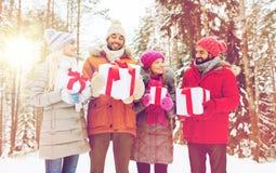 Amis et cadeaux heureux de Noël dans la forêt d'hiver Photo libre de droits