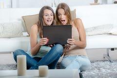 Amis et ordinateur portable heureux Image stock