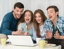 Amis et ordinateur portable heureux Photographie stock libre de droits