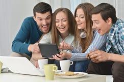 Amis et ordinateur portable heureux Image libre de droits
