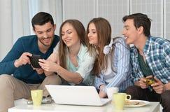 Amis et ordinateur portable heureux Photos stock