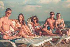 Amis ethniques multi avec des boissons détendant sur une plage Photos libres de droits