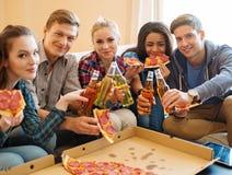 Amis ethniques multi avec la pizza et les bouteilles de la boisson Image stock