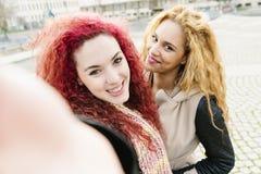 Amis ethniques multi ayant l'amusement dans la ville prenant le selfie Images libres de droits